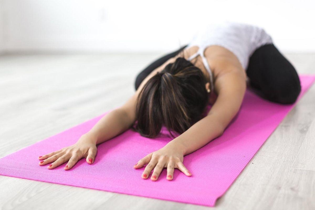 Frau dehnt sich auch ihrer Yoga-Matte